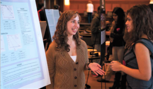 Students talk in front of presentation easel
