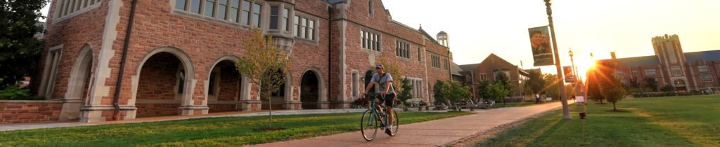 student riding a bicycle new career center