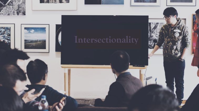"Class and instructors look at board that says ""Intersectionality"""
