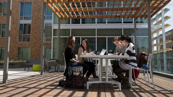 Students sitting at a table outdoors at the lofts