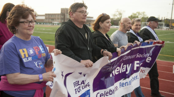 People walking holding Relay for Life Banner