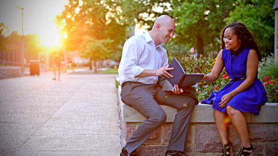 Two people look at a book together on campus