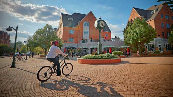 Student riding a bike near the Clocktower at the South 40