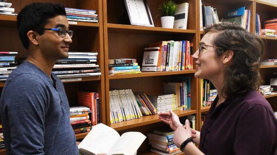 Career Center Adviser in front of Library Shelves