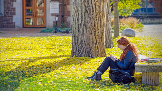student with fall leaves