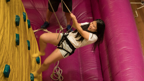 A student climbs an inflatable rock wall during Sup All Night.